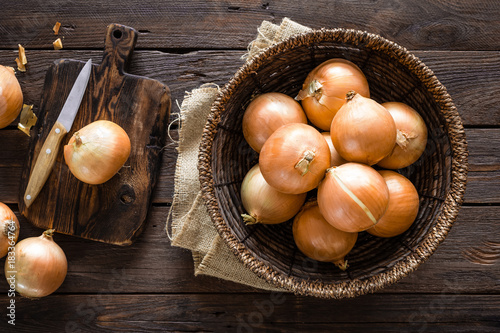 Foto Murales Fresh onion in basket on wooden table, top view