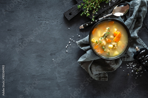 Fresh fish soup in bowl on dark background, top view - 183364983