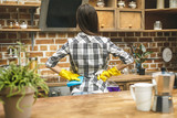 Beautiful woman in the kitchen wiping dust using a spray and a duster while cleaning her house. - 183365167