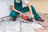 Renovation of old floor. Demolition of old tiles with jackhammer. - 183371346
