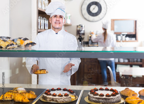 Portrait of middle aged man baker with tasty cakes smiling in bakery