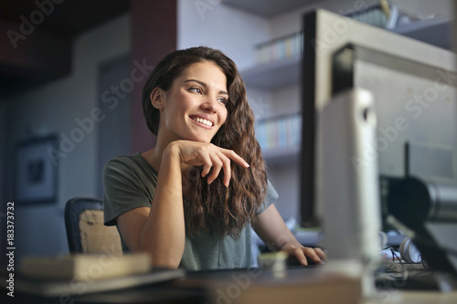 Foto op Canvas Wanddecoratie met eigen foto Smiling woman working at the pc