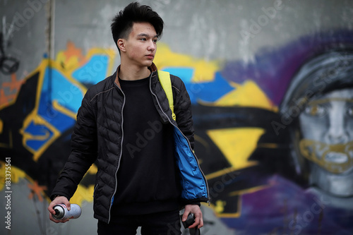 Aluminium Graffiti Asian young man on the street posing at the camera