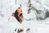 Happy young woman blowing in the snow in his hands, outdoors in winter - 183375977