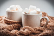 Cocoa or coffee with marshmallows in a white cup with a brown knitted winter scarf. Beautiful christmas background
