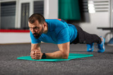 Fitness trainer doing planks in the gym - 183384736