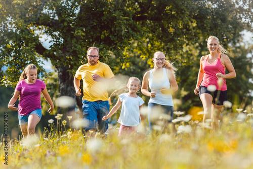 Deurstickers Jogging Familie beim Jogging über eine Wiese mit Blumen im Sommer als Sport
