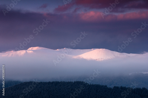 Fantastic landscape of winter mountains at sunrise. View of dramatic cloudy sky and snow-capped peaks in the distance.