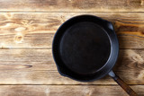 Vintage cast iron pan on wooden rustic background. Top view with copy space. - 183391955