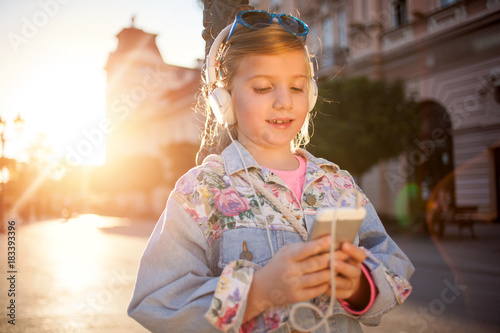 Fotobehang Muziek happy girl child listen to the music from her smartphone