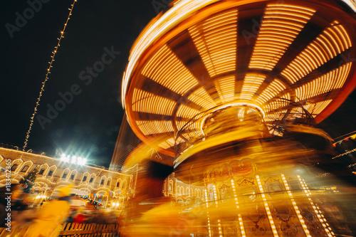 Carousel fast turning in motion illuminated at night