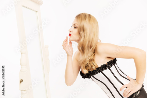 Young beautiful woman in a sexy corset looks in the mirror