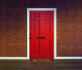 Bright red front door and welcome mat with wood porch floor. - 183413720