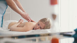 Male physiotherapist massaging woman's back in the medical office - 183428147