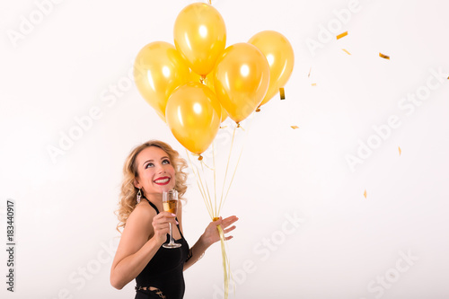 Blonde party woman holding glass of champagne and a lot of yellow balloons.