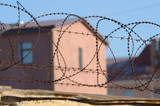Barbed wire on the prison walls. - 183445132