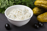 A bowl of white sauce, cucumbers, dill and olives ingredients