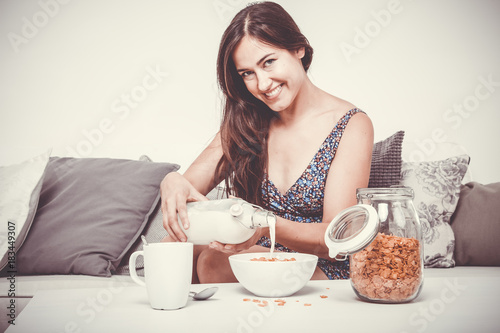 teenager has breakfast with cereals and milk sitting on the sofa in her living r Plakát