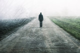 Man standing and gazing on rural foggy and misty grunge textured asphalt road. - 183452764