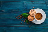 Coffee and oatmeal chocolate cookies on a wooden background. Coffee beans. Top view. Free space for text.