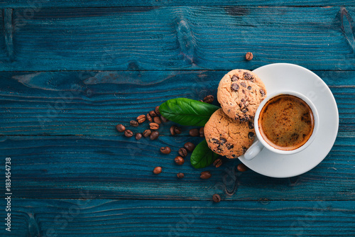 Wall mural Coffee and oatmeal chocolate cookies on a wooden background. Coffee beans. Top view. Free space for text.