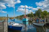 Fischerboote im Hafen des Fischerdorfes Gothmund am Fluss Trave - 183460369