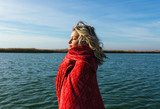 Portrait of young woman by the lake wrap around in a red blanket. - 183465993