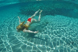 Young woman swims at the bottom of an exotic beach on underwater view - 183471330