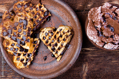 Foto op Canvas Chocolade Belgian heart shaped waffle on brown plate, with hot chocolate with marshmallow on wooden background.