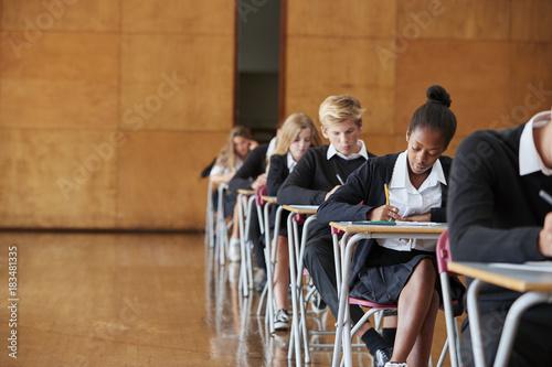Teenage Students In Uniform Sitting Examination In School Hall