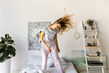 cheerful young woman in pajamas dancing on bed in morning at home - 183482132