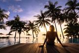 Fototapety Woman enjoying vacation holidays luxurious beachfront hotel resort swimming pool