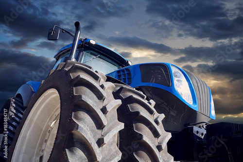 Powerful tractor on sunset background