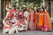 Quadro Beautiful Indian newlyweds stands with their bridesmaids and groomsmen dressed in saris, sherwanis, lehengas outside and look cheerful