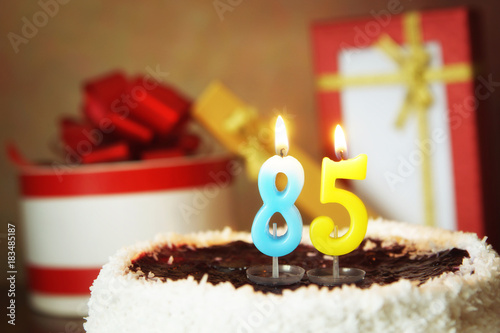 Poster Eighty five years birthday. Cake with burning candles and gifts
