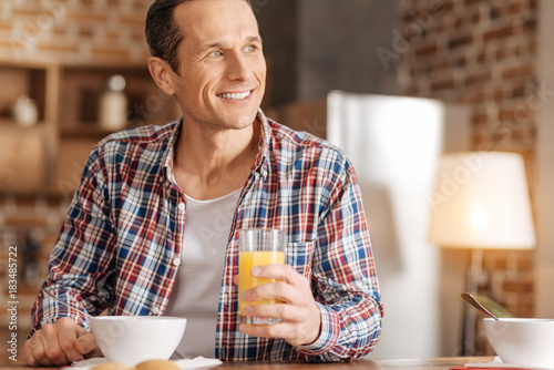 Enjoying vitamins. Pleasant young man sitting at the kitchen table, drinking orange juice and looking at the distance, smiling brightly