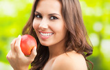 Young happy smiling woman with apple, outdoors - 183486322