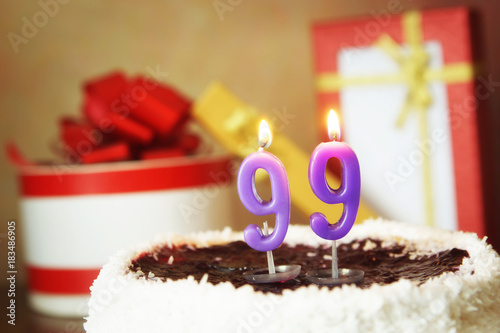 Ninety nine years birthday. Cake with burning candle and gifts Poster