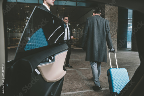 Foto Murales businessman going with blue bag on wheels to airport