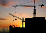 two hoisting cranes above building at sunset - 183490312