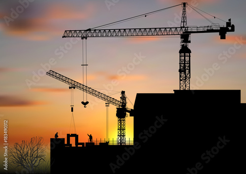 two hoisting cranes above building at sunset