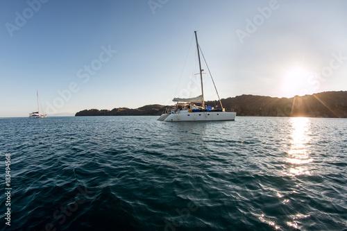 Ein Segelboot / Katamaran ankert in einer einsamen bucht vor Madagaskar Poster