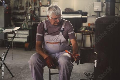 Senior man in workshop. Man lied fire in workshop.