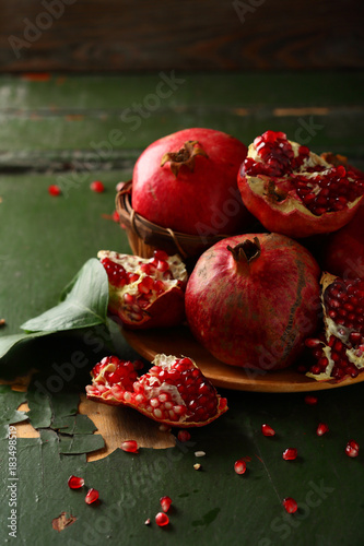 Foto op Canvas Sap Fresh and ripe pomegranates on green wood