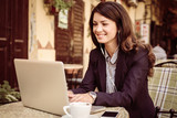 Smiling business woman working on laptop at cafe. - 183498921