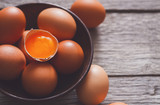 Fresh brown eggs in bowl on wood background - 183501757