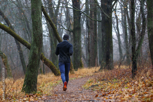 Staande foto Jogging Trail running in autumn park. Back view of young man jogging in fall misty forest