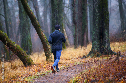 Fotobehang Hardlopen Trail running in autumn park. Back view of young man jogging in fall misty forest