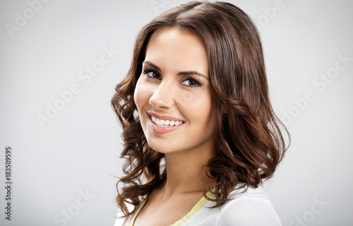 Smiling beautiful young woman, on gray