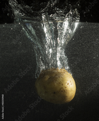 Turnip in water with splashes on a black background